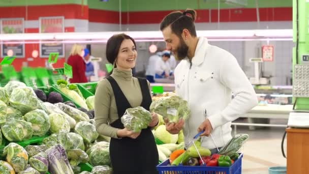 Happy couple buying cauliflower at grocery store or supermarket. Vegetarianism.