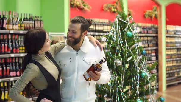 Happy couple buying cognac in a shop standing near a decorated Christmas tree.