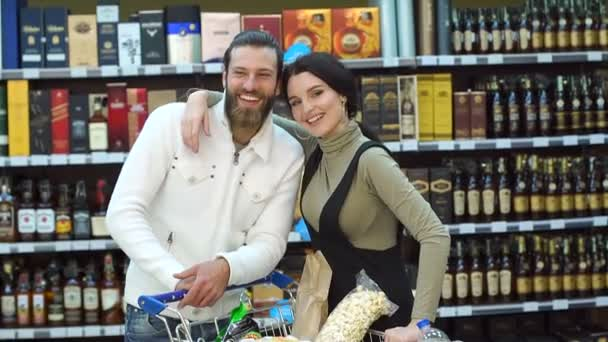 Portrait of a couple in a wine shop with a full cart of products.