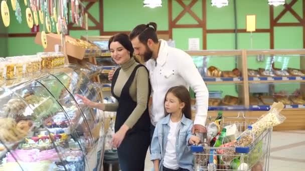 Portrait of family choosing bread and sweets in bakery section in supermarket