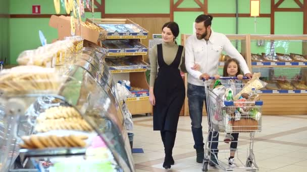 Portrait of family choosing bread and sweets in bakery section in supermarket.
