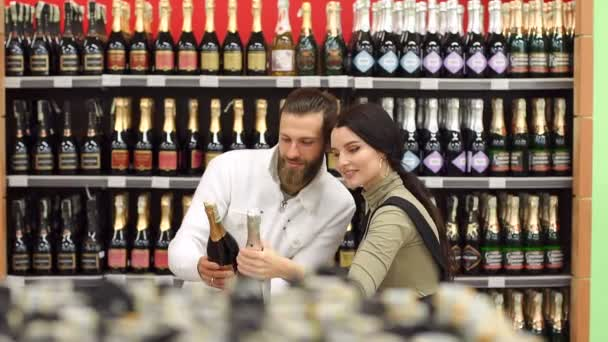 Beautiful young smiling couple while choosing champagne at the supermarket.