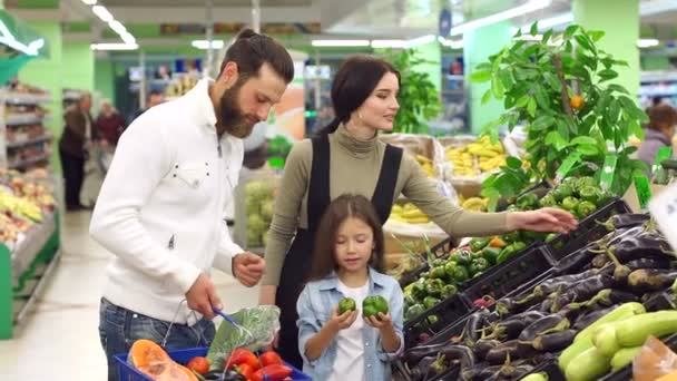 Happy parents with a child choose fresh vegetables and put them in a basket.
