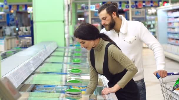 A young couple buy frozen berries in a supermarket standing near a refrigerator.