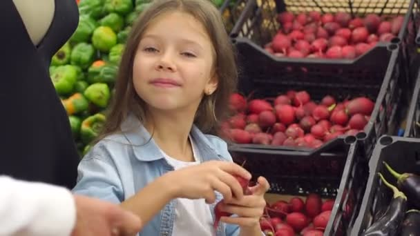 Close-up of little girl buys fresh radish with their parents in the supermarket.