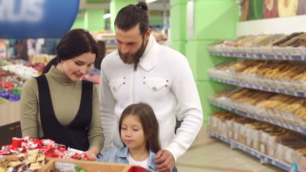 Šťastná rodina s dítětem, cukroví a sladkosti v supermarketu. Zpomalený pohyb