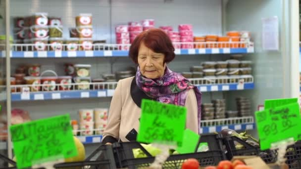 An elderly woman with wrinkles on her face chooses products in the supermarket.