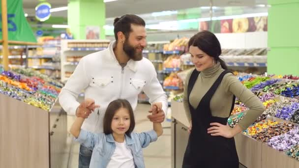 Happy family with a child buying candy and sweets in the supermarket.Slow motion