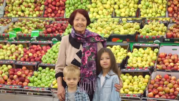 Happy elderly woman with grandchildren in supermarket buys fruit. Portrait.