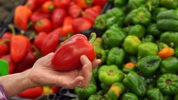 Detailní záběr rukou starší žena s vrásky drží červenou paprikou v supermarketu