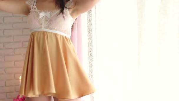 Erotisches junge Mädchen in sexy kurzes Negligé steht am Fenster.