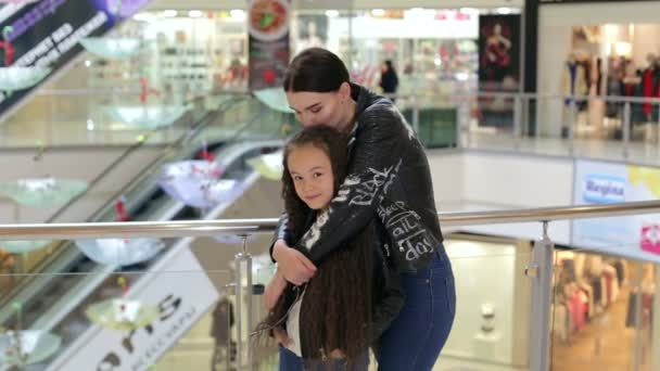 Happy mom in a leather jacket hugs her daughter in a large shopping mall.