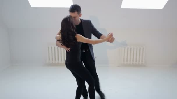 Dancing young couple on a white background. Passionate salsa dancers.