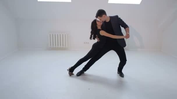 A man and a woman dance a sensual dance of salsa or bachata in a white studio.