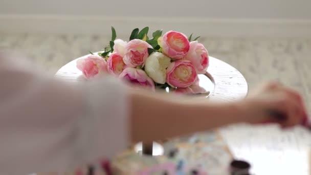 Egy zár-megjelöl egy művész festés virágot egy ecsettel, és a paletta.