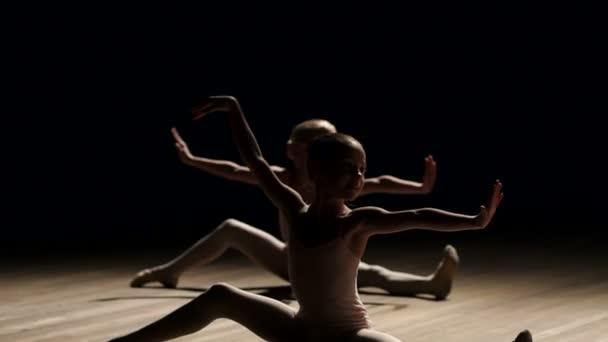 Dvě malé dívky tanečnice taneční balet na scéně ve tmě na dřevěnou podlahu.