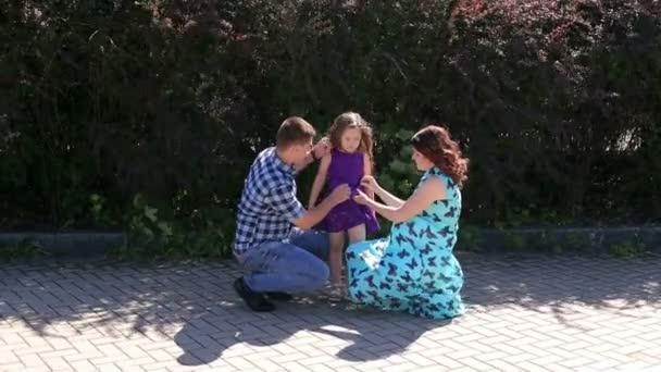 Familie. Vater, schwangere Mutter und Tochter im Freien. Spaziergang im Stadtpark.