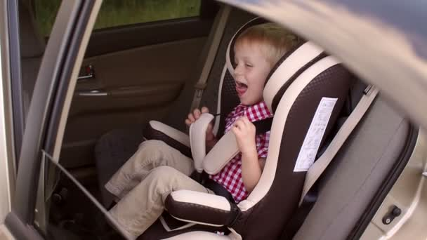 Portrait of a happy laughing boy in a car seat in the car.