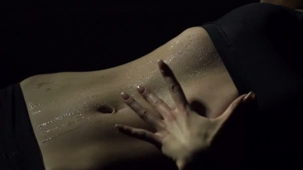 Close-up on the belly of a girl pouring water. Slow motion.