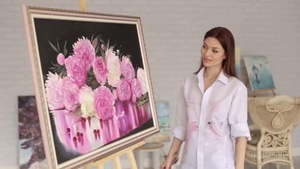 Portréja egy művész lány közelében egy képet, a pünkösdi rózsa virág.