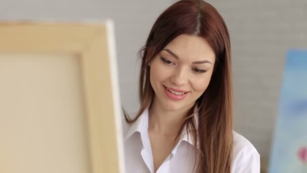 A young sexy girl in a white shirt draws on canvas in the studio for drawing.Art
