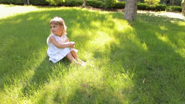 Édes kislány ül a fűben, a parkban, portré.