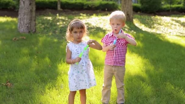 Malý bratr a sestra vyfukuje bubliny na trávě v parku.