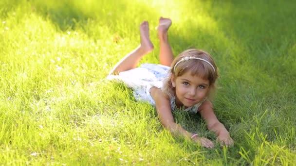 Malá roztomilá dívka v bílých šatech, ležící na zelené trávě v Sunny Park v horkém počasí. Neobvyklé dívka s jinou barvou očí v parku, portrét.
