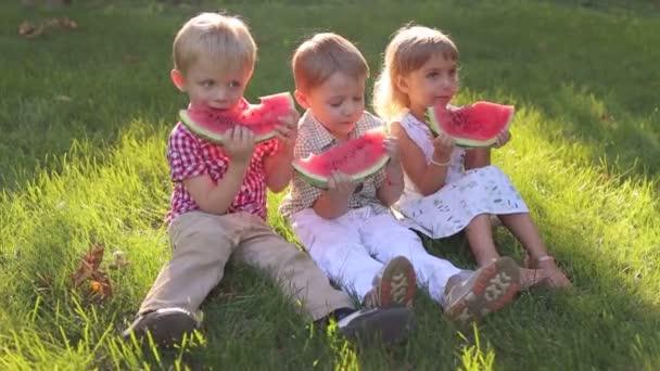 Tři veselá šťastné děti jíst meloun v létě v parku.