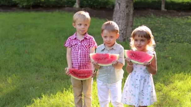 Tři roztomilé malé děti jíst meloun v létě Sunny Park v horkém počasí