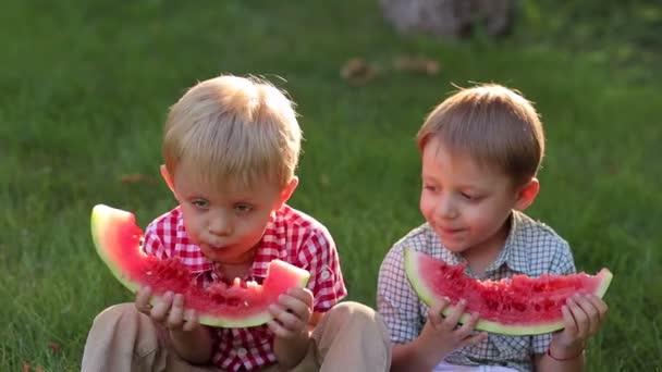 Dvě malé děti jíst meloun v letním parku sedí na zelené trávě