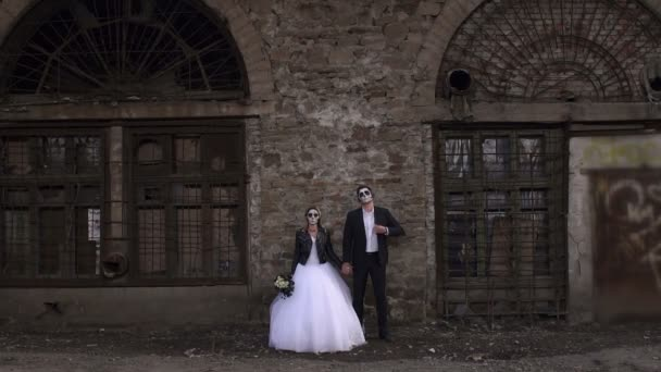 Creepy couple in a wedding dress with makeup for Halloween stand near brick wall