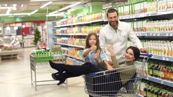 Portrét happy fun rodina v supermarketu, Máma sedí v nákupním vozíku