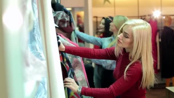 Vásárlás ruházati bolt három gyönyörű fiatal nő portréja.