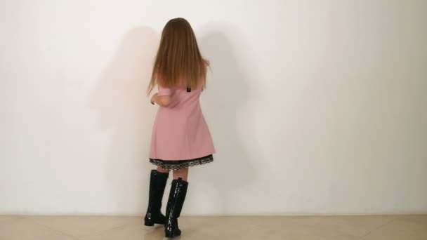 Malá holčička v růžových šatech a černé boty na spinning Studio na bílém pozadí