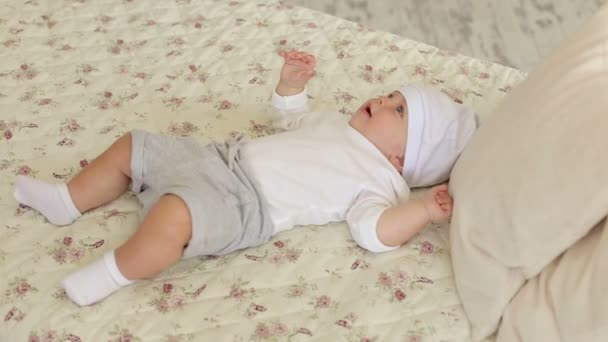Close-up of a newborn cute boy in a white hat lying on a bed at home.