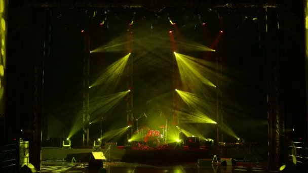 Yellow light flashing on an empty stage in the dark. Stage lighting.