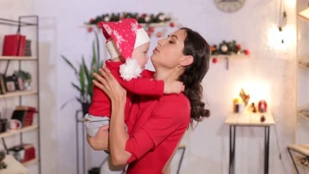 Porträt einer Mutter mit einem kleinen Neugeborenen für Weihnachten zu Hause.