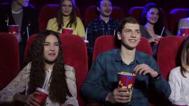 Tinédzser baráti a moziban, filmnézésre és pattogatott kukoricát eszik.