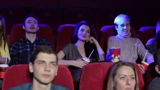 Gruppe Jugendlicher Freunde im Kino, die sich einen Film anschauen und Popcorn essen.