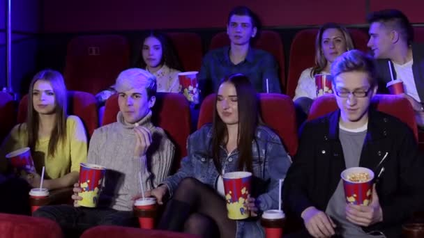 Young friends sit in a cinema with popcorn and drinks and watch a comedy film.