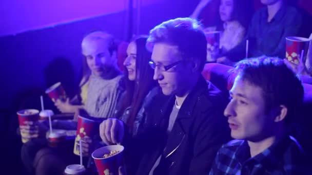 Fiatal meg egy mozi pattogatott kukorica és italok ülni, és nézni egy vígjáték.