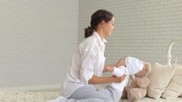Egy fiatal anya egy újszülött otthon az ágyra portréja.