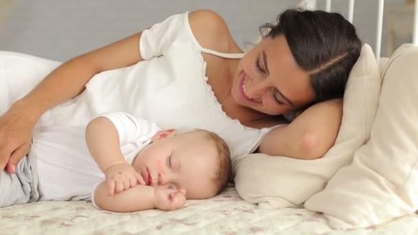 Šťastná maminka leží s její spící novorozeně v posteli