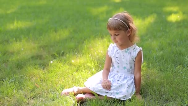 Little girl in summer dress and with hair Hoop sitting on green grass in Park.