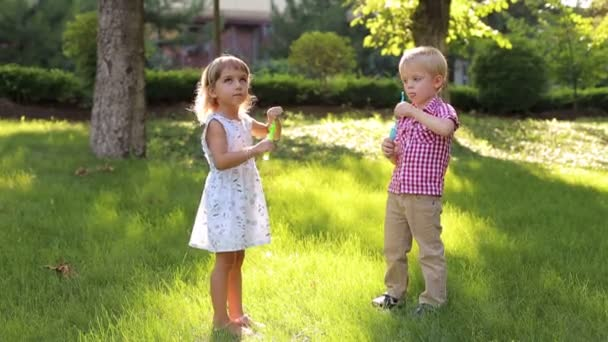 Little brother and sister blowing bubbles on the grass in the Park.