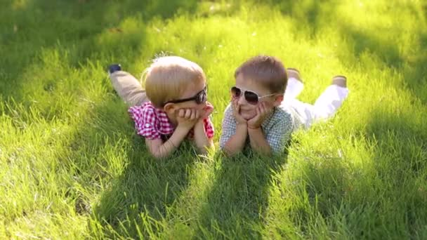 Two cheerful happy little boys lie on the grass in sunglasses in summer.
