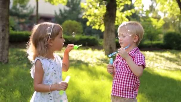 Kis testvérpár buborékokat eregetett a füvön, a parkban.
