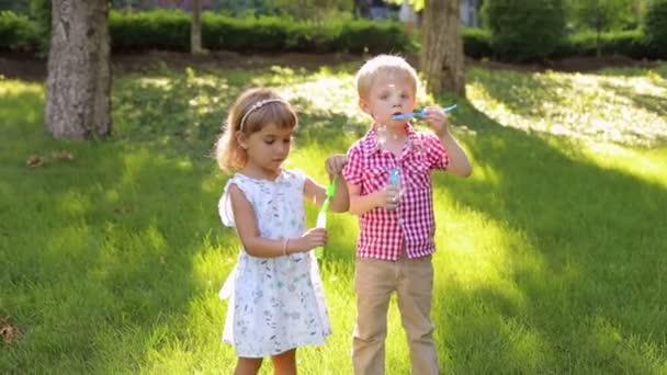 Geschwisterchen pustet Blasen auf dem Gras im Park.