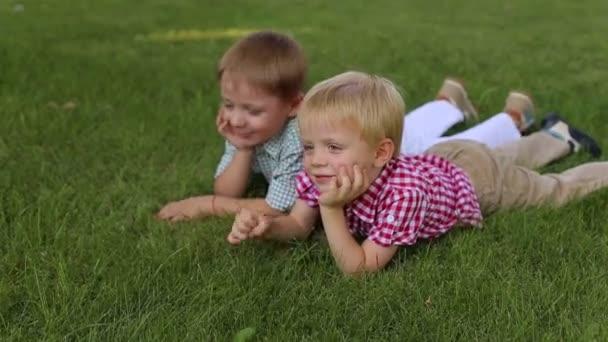 Dva roztomilý malí kluci v košilích leží na zelené trávě a usmívá se.